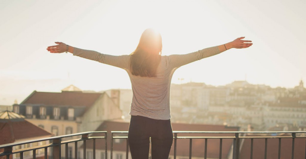 woman with high self-esteem and confidence raises arms on balcony