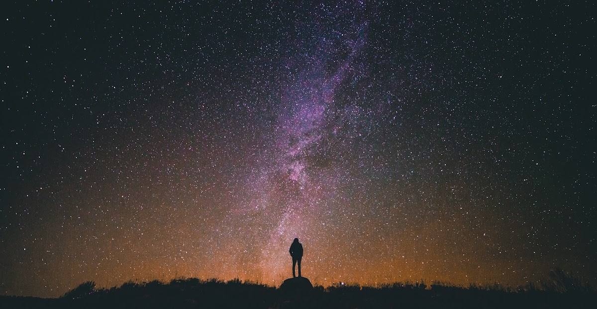 a man standing and looking at the milky way galaxy, contemplating the law of attraction by jack canfield