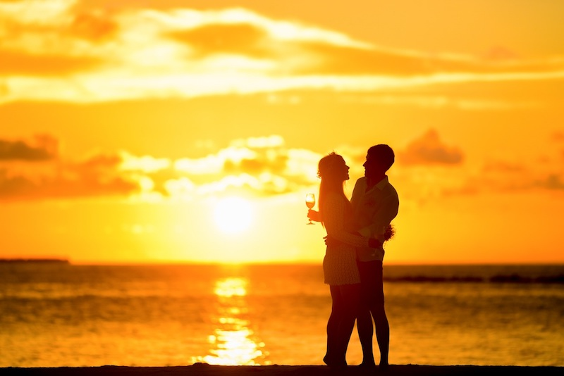 A couple embracing during a beach sunset use the law of attraction for relationships by jack canfield