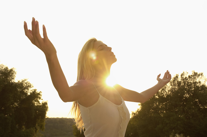 a woman meditating at sunset using the law of attraction by jack canfield